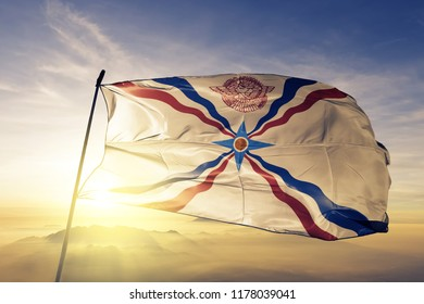 Assyrian people flag textile cloth fabric waving on the top sunrise mist fog