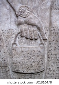 Assyrian relief 865-860 BC, showing Cuniform script, of a royal helper carrying a bucket