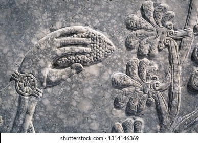 Assyrian wall relief of a genius, detail with a cone in a hand. Ancient carving panel from Mesopotamia. Remains of the culture of ancient Assyrian and Sumerian civilization in the Middle East.