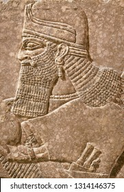 Assyrian wall relief of a genius from Mesopotamia, detail with a head. Ancient carving panel from the Middle East history. Remains of the culture of ancient Assyrian and Sumerian civilization.