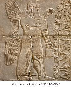 Assyrian wall relief of a winged genius with cuneiform. Ancient carving panel from the Middle East history. Remains of the culture of ancient Assyrian and Sumerian civilization.