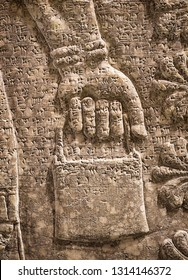 Assyrian wall relief of winged genius, detail with a hand. Ancient carving panel with cuneiform of Mesopotamia. Remains of the culture of ancient Assyrian and Sumerian civilization in the Middle East.