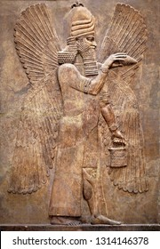 Assyrian wall relief of a winged genius. Ancient carving panel from the Middle East history. Remains of the culture of ancient Assyrian and Sumerian civilization. Art of Mesopotamia.