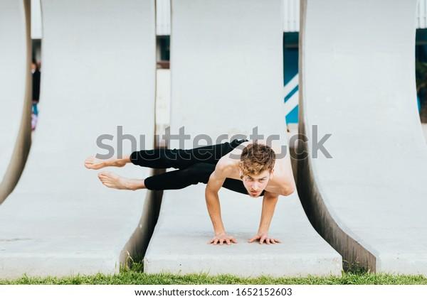 astakrasana, una asana de yoga de ocho ángulos para fortalecer los antebrazos entrenados por un joven atleta.