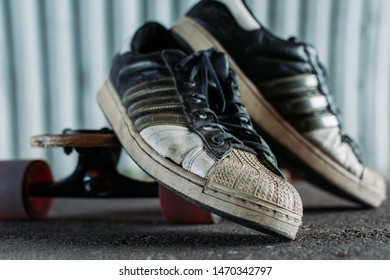 Astana. Kazakhstan. August 4, 2019. Old Adidas Sneakers. Sneakers stand on a longboard. Longboard stands in the tunnel.