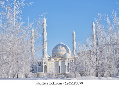 Astana, Kazakhstan - December 21, 2017: Beautiful winter landscape of Astana. Frozen trees in a cold city in winter against the sky. View of the mosque Hazaret Sultan. New Year background - Image