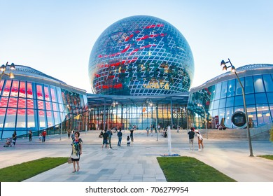 "Astana, Kazakhstan - July 29, 2017: The main building of the Expo 2017 in Astana this is Exhibition Complex - ""Nur Alem"". In the photo, people are walking in street capital of Kazakhstan."