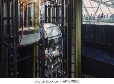 Astana, Kazakhstan - July 4, 2017: Glassed-in elevators in Kazakhstan pavilion. People in elevator looking upwards
