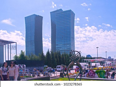 Astana, Kazakhstan - July 6, 2017: View of streets of Astana. People, residential buildings, street sculpture of camel with shanyrak (sacred part of yourt), poster of opera 'Abai'. Selective focus