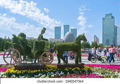 Astana, Kazakhstan - July 6, 2017: Interesting topiary installation of carriage with passengers, coachman & horse made of boxwood against beautiful view of modern city.