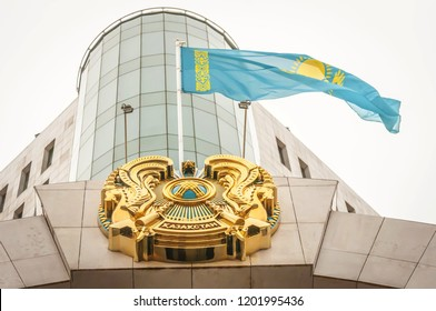 ASTANA, KAZAKHSTAN. October 12, 2018. Flag of Kazakhstan and coat of arms over the main entrance to the Kazakhstan Senate building in downtown Astana. Republic of Kazakhstan state parliament concept.