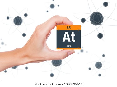 Astatine element symbol handheld and atoms floating in background