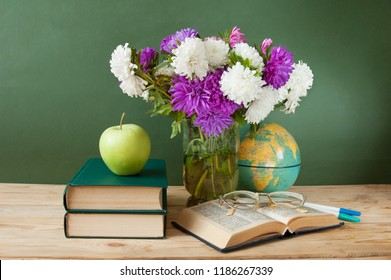 asters flowers bunch, books and apple on artistic background, still life, teacher's day concept