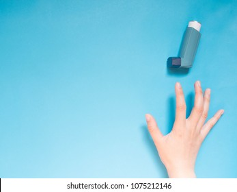 Asthma and COPD disease concept. Young female hand trying to reach blue asthma inhaler for relief asthma attack symptoms on light blue background with copy space for text. Top view. Minimal style.
