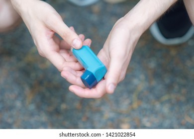Asthma medecine inhaler holded by two hands of a man