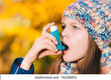 Asthma patient girl inhaling medication for treating shortness of breath and wheezing in a park. Chronic disease control, allergy induced asthma remedy and allergy disease concept