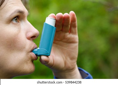 Asthma patient inhaling medication for treating shortness of breath and wheezing. Chronic disease control, allergy induced asthma remedy and chronic pulmonary disease concept.