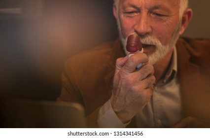 Asthmatic attacks are difficult. Man using asthma inhaler.