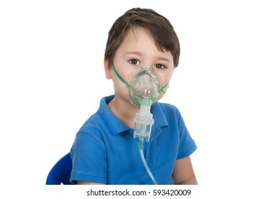 Asthmatic boy having a medical inhalation. Wearing face mask from nebulizer inhaler machine. Isolated on a white background.