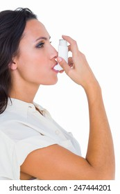 Asthmatic brunette using her inhaler on white background