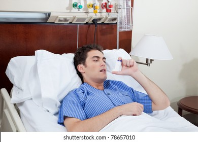Asthmatic male patient on bed using asthma inhaler