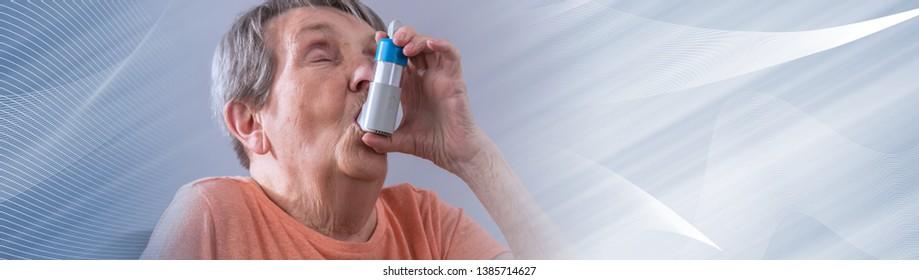 Asthmatic senior woman using an inhaler. panoramic banner