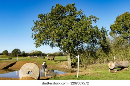 Aston le Walls, Northamptonshire. England- October 21, 2018: Competitor negotiating a water hazard at a free to public horse trial. Bright sunshine with reflections in water.