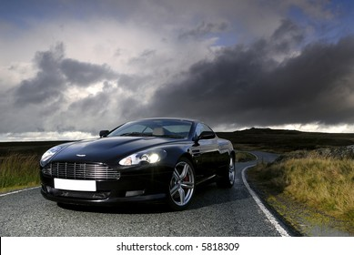 Aston Martin DB9s under a stormy sky