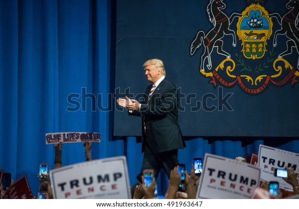 ASTON, PA - SEPTEMBER 22, 2016: Donald Trump enters the stage and walks by the state flag of Pennsylvania. Trump held a rally at Sun Center Studios as the republican nominee for US President.