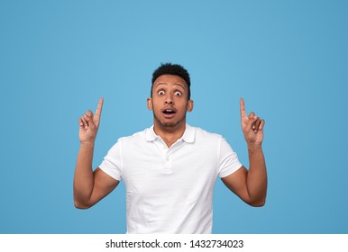 Astonished African American man looking at camera and pointing on empty space over head against blue background