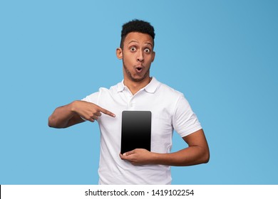 Astonished African man in white polo shirt looking at camera and demonstrating tablet with empty display for text against blue background