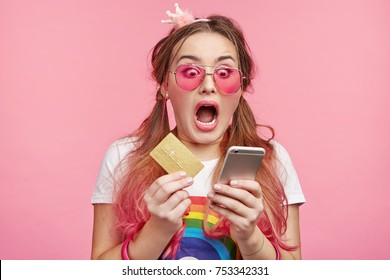 Astonished amazed stylish fashionable woman with two pony tails and pink trendy sunglasses realizes that she is short of money, has no opportunity to make purchase online. Interent and shopping