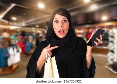 Astonished Arab woman receiving surprising news online in a smartphone. super discount.