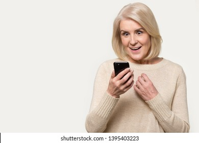 Astonished blond middle aged female holding wireless device looking at cellphone screen received sms promotion discount sell-out unbelievable offer isolated on grey copy space background concept image