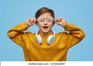 Astonished boy adjusting stylish glasses and looking at camera against blue background