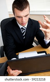 Astonished businessman looking at his laptop sitting in his office