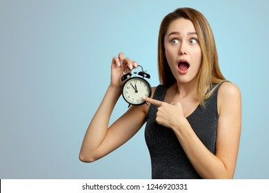 Astonished girl opens her mouth wide in surprise and shows the clock. Five to twelve minutes. Isolated on blue background.