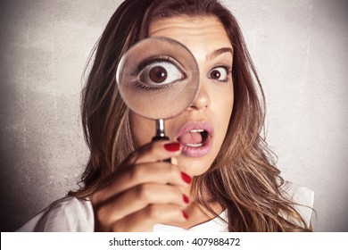 Astonished girl using magnifying glass