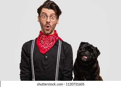 Astonished handsome male with stupefied expression, stands near his favourite pet, feels care and responsibility, take pleasure of playing together, isolated on white background. Surprisement concept