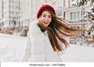 Astonished happy girl in red hat having fun in frozen morning on street full with snow. Expressing positivity, true cheerful emotions, waiting for christmas, winter holidays mood, smiling