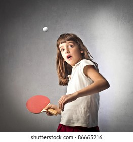 Astonished little girl playing ping pong