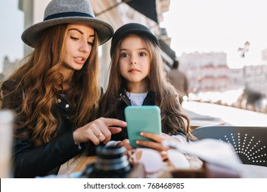 Astonished long-haired little girl holding blue smartphone, while her mom pointing with finger at something important. Portrait of stylish woman in felt gray hat and her charming daughter in cafe