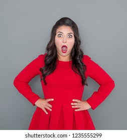 Astonished Plus size woman in red dress on gray background