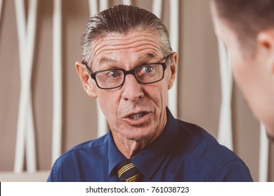 Astonished Senior Businessman Talking to Young Man