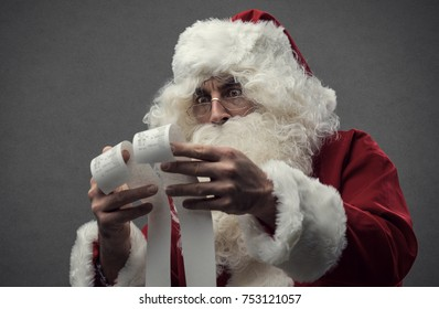 Astonished shocked Santa Claus checking Christmas's shopping expensive bills, he is holding two long receipts