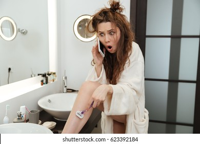 Astonished shocked young woman in bathrobe shaving legs and talking on mobile phone in bathroom