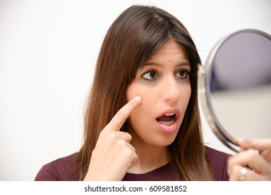 astonished woman with dark circles in the mirror