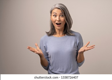 Astonished Woman of Mongolian Appearance with Gray Hair Against the Background of Gray. Her Eyes and Mouth are Wide Open with Surprise. With Her Hands She Demonstrates An Incomprehensible State. Close