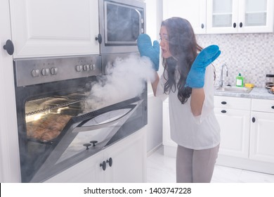 Astonished Woman Standing In Front Of Burning Oven With Smoke Around Kitchen