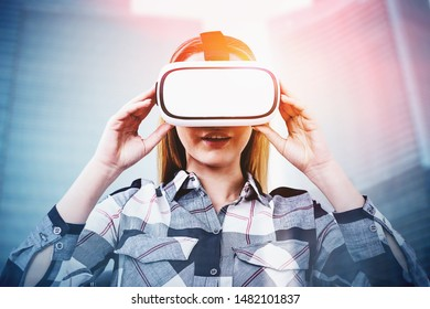 Astonished young blonde woman in checkered shirt and VR glasses over blurred city background. Concept of virtual tourism and hi tech. Toned image